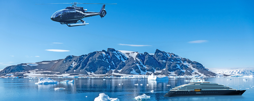 helicopter flying over snow capped mountains